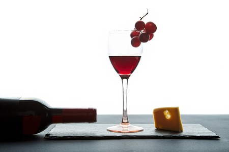 Glass of red wine beside bottle and traditional appetizer on white background.
