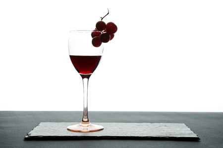 Glass of red wine garnished with grape on white background. Stock Photo