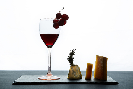Glass of red wine garnished with grape and pieces of savory cheese.