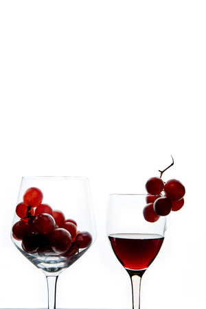 Crystal glasses with red grape and tasty wine on white background.