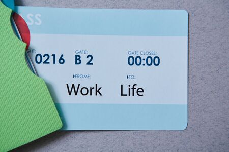 Work life balance choice concept. Boarding pass and a notebook on a gray background Banco de Imagens