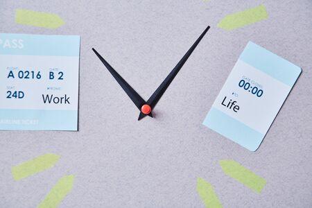 Work-Life-Balance-Wahlkonzept. Uhrpfeile zwischen Bordkartenteilen mit Aufschriften