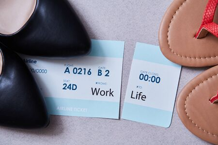 Work life balance choice concept. Boarding pass cut in two between office shoes and flip flops. Imagens