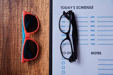 Work life balance choice concept: colored sunglasses and strict office glasses Imagens