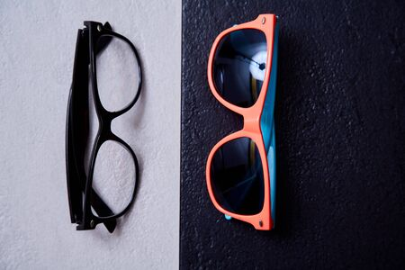 Work life balance choice concept: colored beach sunglasses and strict office glasses. Reklamní fotografie - 124678133