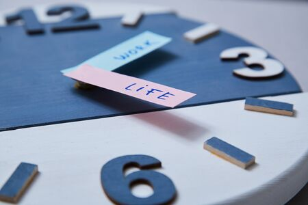 Work life balance choice concept. Clock closeup and arrows telling. Banco de Imagens