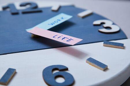 Work life balance choice concept. Clock closeup and arrows telling. Reklamní fotografie