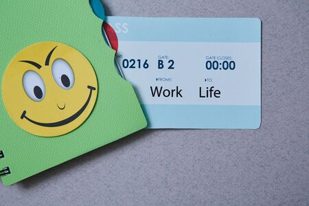 Work life balance choice concept. Boarding pass and a notebook on a gray background. Reklamní fotografie - 124678147