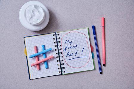Blogging, blog and blogger or social media concept: Notepad, cream jars and hashtag symbol on grey background 版權商用圖片