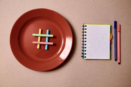 Food blogging, blog and blogger or social media concept: symbol hashtag on the red plate. Flat lay.
