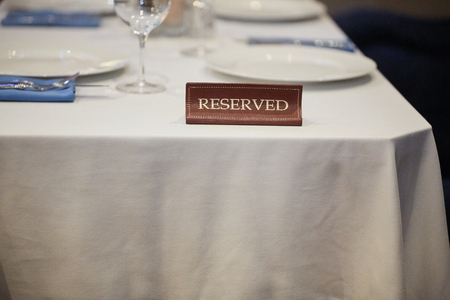 Restaurant reserved table sign with places setting and wine glasses ready for a party. Standard-Bild