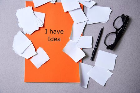 Inspiration, insight or good idea concept: torn paper around a blank orange sheet of paper