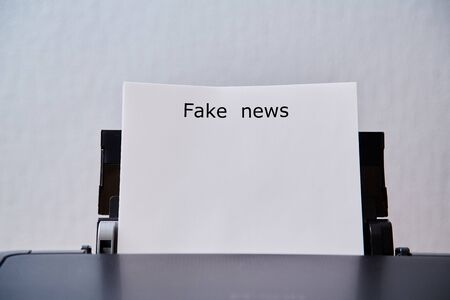 Fake news, disinformation or false information and propaganda concept. Sheet with the inscription in the printer