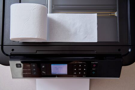 Fake news, disinformation or false information and propaganda concept. A roll of toilet paper, and a printer.