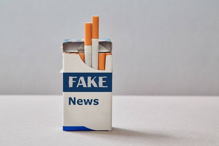 Fake news, disinformation or false information and propaganda concept. A pack of cigarettes with an inscription.