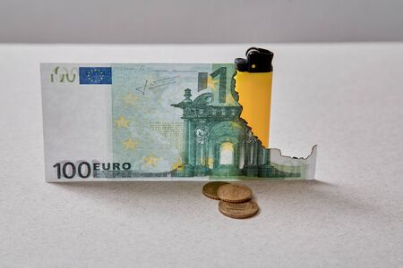 Inflation and depreciation money concept. Bankruptcy or financial ruin and poverty. Burnt Euro banknote and lighter