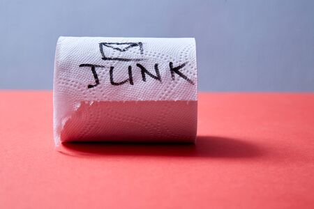 Junk mail or spam e-mail and unsolicited letter idea. Roll of toilet paper with the inscription junk. Standard-Bild