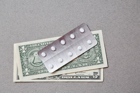 Concept for expensive health care,pharmaceutical and paid medicine. Pills lying on the dollar bills. Banco de Imagens