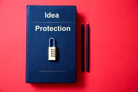 Concept for copyright, patent or intellectual property and idea protection.The lock with the code lying on the book.