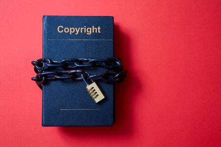 Concept for copyright, patent or intellectual property and idea protection. Book wrapped in a chain with a lock.