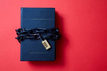 Concept for copyright, patent or intellectual property and idea protection. Book wrapped in a chain with a lock. Imagens
