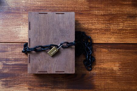 Concept for copyright, patent or intellectual property and idea protection.Box wrapped with chain on lock. Imagens