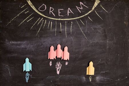 Concept for achieving goal and dream, business motivation: Paper rockets on blackboard