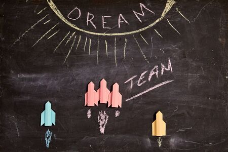 Unity and teamwork concept: Dream team, collaborate and cooperation. Group of paper rockets and the inscription.