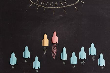 Business organization, corporate subordination, hierarchy and structure: Multicolored paper rockets on a blackboard Imagens