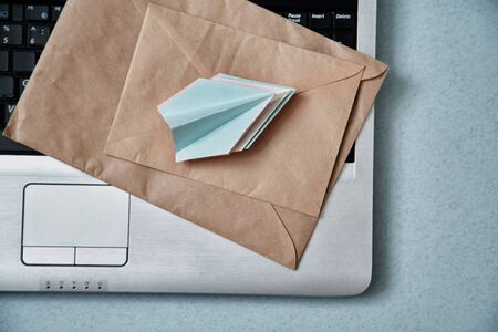 Sending e-mails and e-commerce business. Email marketing or advertising: paper airplanes, envelopes and a laptop