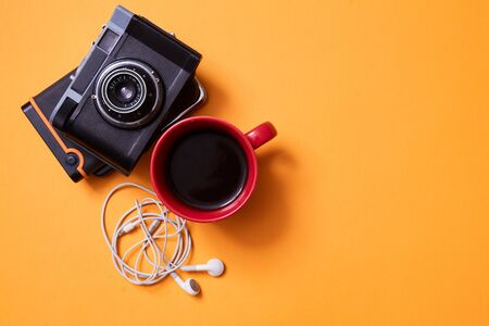 Blogging and traveling. Freelance work, adventure and exploration concept. Vintage camera and a Cup of coffee Reklamní fotografie