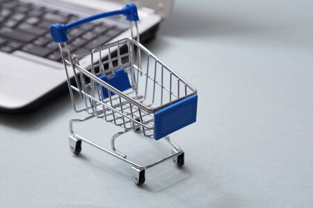Internet e-commerce and shopping online. Basket next a laptop background