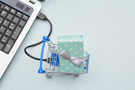 Delivery, online shopping and business concept. Gift lying in the basket and laptop