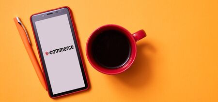 Online shopping and e-commerce. Smartphone and a Cup of coffee on a yellow background