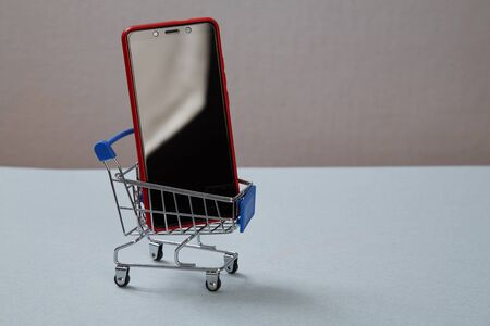 Online shopping and e-commerce. Smartphone and shopping basket