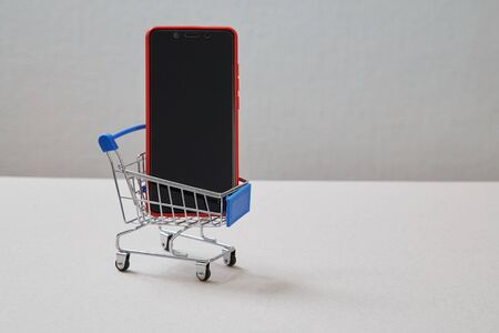 Web store and online shopping concept. Smartphone and shopping basket