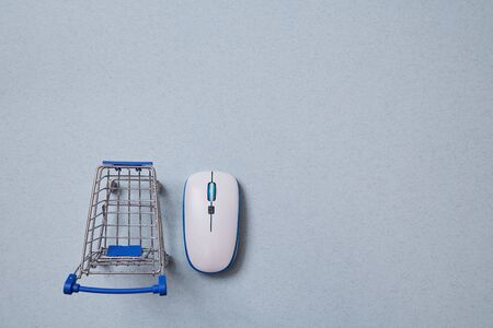 Online market and and shoping. Basket and computer mouse. Background.