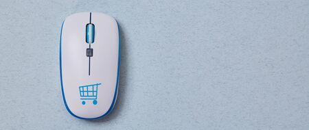 Online shopping, buying and e-commerce. Computer mouse with cymbol of basket. Blue background