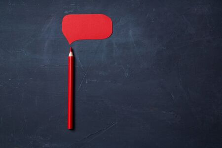 Red pencil and cardboard cloud for writing on a blackboard background. Copy space.