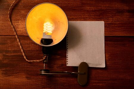 Vintage lamp and a piece of paper for writing on a wooden background. Mock up