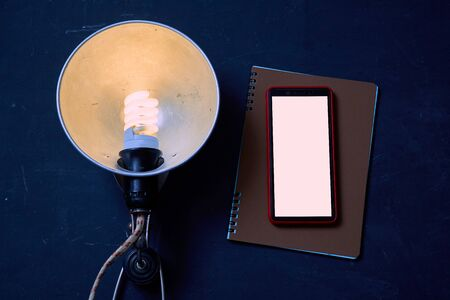 Vintage lamp and smartphone with space for writing lying on the notebook. Blackboard background. Mock up. Reklamní fotografie