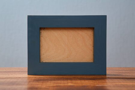 Wooden photo frame with space to insert an image or inscription on a wooden background. Blue background. Mock up. Reklamní fotografie