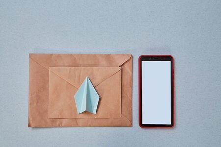 Email marketing and message online, online chat concept: Paper plane , envelope and smartphone. Background, mock up Reklamní fotografie