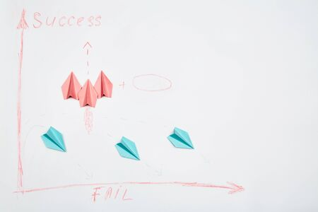 Unity and teamwork concept for business competition: A group of paper planes and origami rockets on a white background