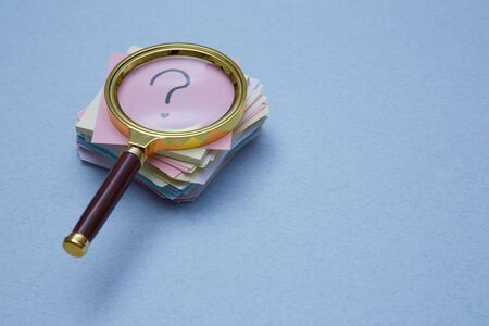 FAQ, Q and A and SEO idea. Question and answer concept. Magnifying glass and sticky note