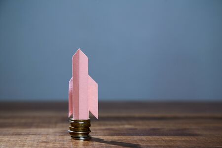 Business, finance, investment, saving and stock market concept. Paper rocket taking off from a stack of coins