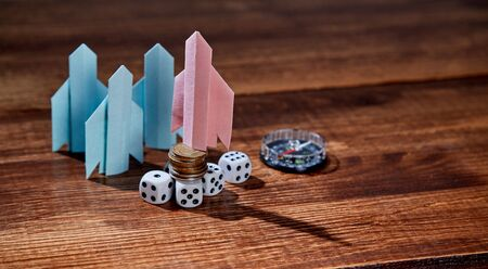 Start up and progress. Aspirations, development and investment concept. Origami paper rocket, dice and compass.