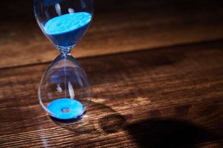 Time passing, deadline, urgency concept. Time management. Blue hourglass on wooden background. Copy space