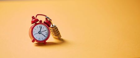 Time management, deadline and urgency concept. Time passing or running out. Clock on the lock, on a yellow background