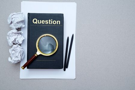 FAQ, Q and A and SEO idea. Question and answer or analysis concept. Magnifying glass, book and crumpled paper